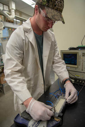 Photo of Tim Foley measuring set time behavior of alkali-activated materal